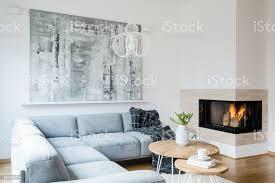 schwarze decke geworfen auf graue ecke lounge innen weiß wohnzimmer mit kamin frische tulpen in vase und große moderne gemälde an der wand hängen