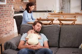 foto auf lager müde vater mit baby sohn schlafen auf sofa als mutter arbeitet