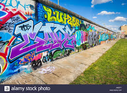 Panoramic View Of Famous Berlin Wall Decorated With Colorful Graffiti Street Art At Historic East Side Gallery On A Sunny Day Blue Sky And Clouds