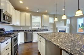 Light Blue Glass Subway Tile Backsplash by Quartz Countertops Painted White Kitchen Cabinets Lighting