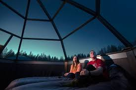 Waiting for northern lights inside an Arctic glass igloo in