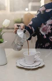 Female Hand Pouring Coffee In A Cup Stock Photo