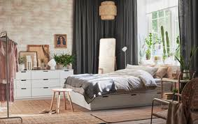 White Bed With Drawers In A Large Bedroom Exposed Brick Grey Curtains And Jute