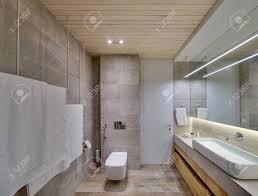 badezimmer in einem modernen stil mit strukturierten fliesen und holzdecke es gibt eine weiße waschbecken auf dem gestell hölzerne schränke