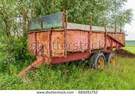 Neglected Old And Rusty Farm Trailer Parked In The Grass Next To A Field