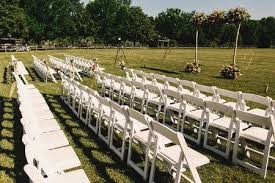 White Garden Chairs Stand In Rows Before A Wedding Altar Stock Photo