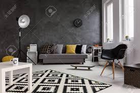 grau wohnzimmer mit sofa stuhl stehle kleine weiße tisch und schwarz und weiß muster teppich