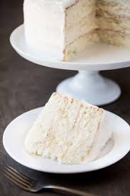 Slice of white cake next to a fork on a white plate with the rest of