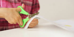 Childs Hands Cutting Paper With Scissors By Garsya