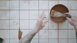 Top View Tattooed Hands Use Palette Knife To Apply Red Tile Adhesive From Tin Pot