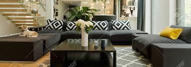 schwarzes modernes sofa mit muster kissen im geräumigen wohnzimmer