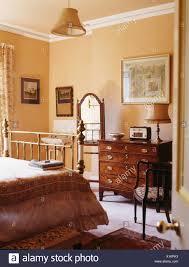 antike kommode und messing bett im schlafzimmer der