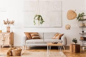 die stilvolle boho kompostion im wohnzimmer interieur mit design grauen sofa holz couchtisch kommode und elegante persönliche accessoires honiggelb