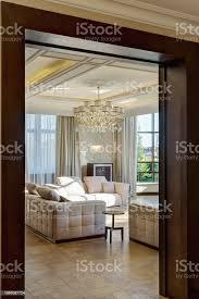 blick vom tor des modernen interieurs des leeren wohnzimmer in den farben beige braun weiß drei sofas mit kissen kristallkronleuchter in der mitte der