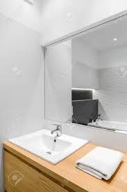 neues weißes badezimmer mit holzschrank stilvollem waschbecken und großem spiegel