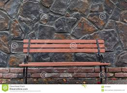 park bench against stone wall stock photo image 85788094