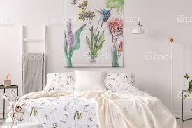 ein pastell schlafzimmer innenraum mit einem bett in grünen pflanzen muster weiße leinen gekleidet stoff in blumen und vögel auf dem hintergrundwand