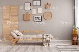 galerie plakaten in schwarzen rahmen und korb kinckknack auf beige wand trendigen wohnzimmer interieur mit langen sofa mit kissen und decke