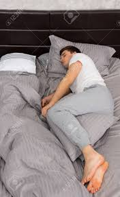 gut aussehend müde mann im pyjama allein ohne decke im stilvollen bett in grauen farben und in der nähe nachttisch in einem schlafzimmer im