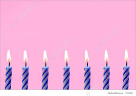 Bottom border of blue and white striped lit birthday candles on pink background