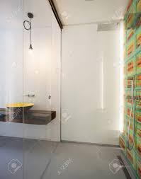modernes badezimmer große dusche und gelbes waschbecken im hintergrund