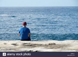 A Man Sitting At The Cliffs Edge Looking Out To Sea
