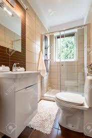 kleines badezimmer mit verglaster dusche wc und spiegel über dem waschbecken