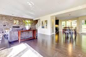 schöne moderne große helle wohnzimmer mit dunklem boden und steinmauer