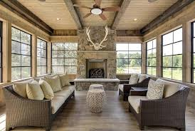 Country Cabin Sunroom With Antlers Over Fireplace