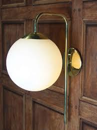 polished brass wall light with opal glass globe light