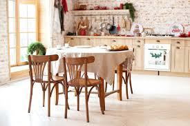 helles esszimmer mit esstisch aus holz stühlen und küche im
