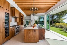 The Customized Walnut Kitchen Opens To Outdoors And Features Leathered Perla Venata Quartzite Countertops
