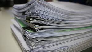 Working In Stack Of Paper Files On Work Desk Office