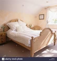 weiße bettwäsche auf kiefer bett im schlafzimmer mit