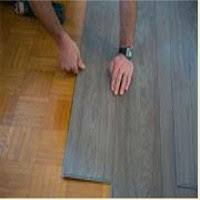 Image Link To Vinyl Flooring Section Featuring An Installers Arms And Hands In The Foreground