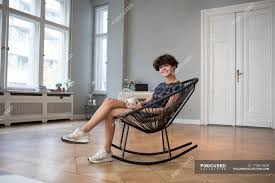 Portrait Of Smiling Young Woman Sitting On Rocking Chair At ... Rocking Chair For Nturing And The Nursery Gary Weeks Coral Coast Norwood Inoutdoor Horizontal Slat Back Product Review Video Fort Lauderdale Airport Has Rocking Chairs To Sit Watch Young Man Sitting On Chair Using Laptop Stock Photo Tips Choosing A Glider Or Lumat Bago Chairs With Inlay Antesala Round Elderly In By Window Reading D2400_140 Art 115 Journals Sad Senior Woman Glasses Vintage Childs Sugar Barrel Album Imgur Gaia Serena Oat Amazoncom Stool Comfortable Cushion