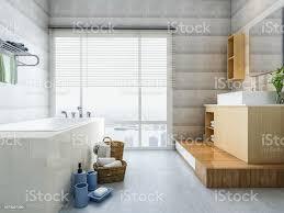 modernes und geräumiges badezimmer design mit einer badewanne waschtisch und waschmaschine sowie grünpflanzen sonnenlicht durch große deckenhohe