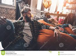 Man And Woman Resting On Beanbag Chair In Messy Room After ...