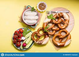 salzbrezel weiße bavarianische würstchen und gemüse auf