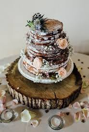 A Naked Chocolate Wedding Cake Dusted With Powdered Sugar And Sitting Atop Rustic Wooden