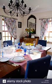 Wrought Iron Chandelier Above Blue Chairs And Table Set For Lunch With White Crockery Glasses In Country Dining Room