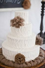 Four Tiered White Wedding Cake Decorated With Burlap Flowers