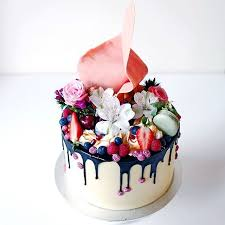 Cakes By Cliff vanilla layered buttercake with Swiss meringue buttercream topped with mixed berries macarons fresh flowers a huge pink sail