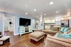 pastell blaue wände im keller wohnzimmer innenraum mit offenem grundriss große ecksofa mit blauen kissen und hocker vintage weiße und blaue