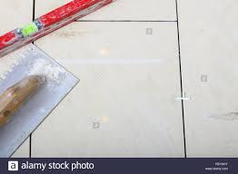building work tool notched trowel level on tile floor surface