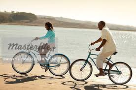 Smiling Father And Daughter Riding Their Bikes Alongside A Beach