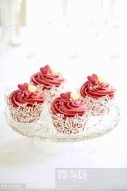 Cupcakes With Pink Icing And Sugar Hearts In White Butterfly Cake