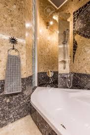 ethnische badezimmer interieur mit gold und grau colous mit großer badewanne dusche mosaik an der wand und handtuch