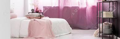schwarze regale und rosa vorhänge im schlafzimmer der frau mit kissen und decke auf weißem bett