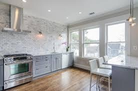 gray kitchen cabinets with marble mini brick tile backsplash